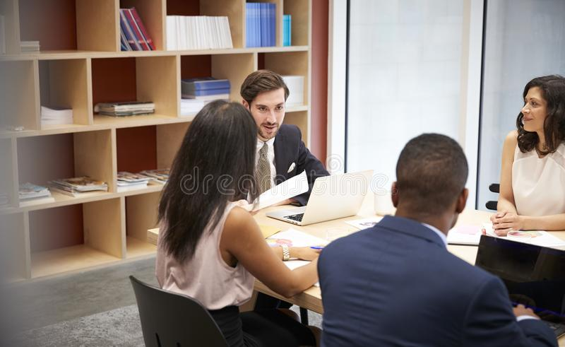 Cuatro hombres de negocios en una reunión de la sala de reunión imágenes de archivo libres de regalías