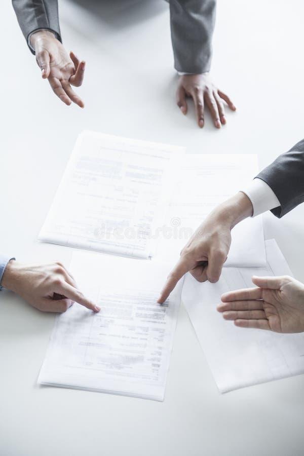 Cuatro hombres de negocios que discuten y que gesticulan alrededor de una tabla durante una reunión de negocios, manos solamente imagen de archivo
