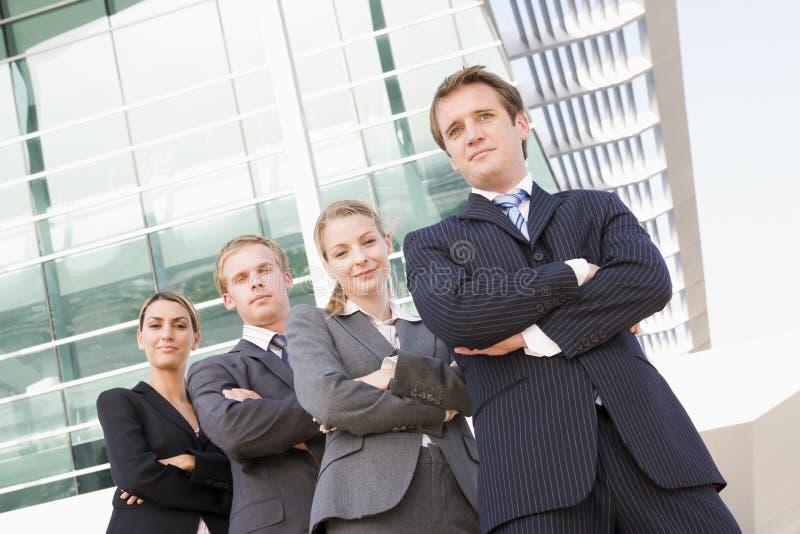 Cuatro hombres de negocios que se colocan al aire libre sonrientes foto de archivo
