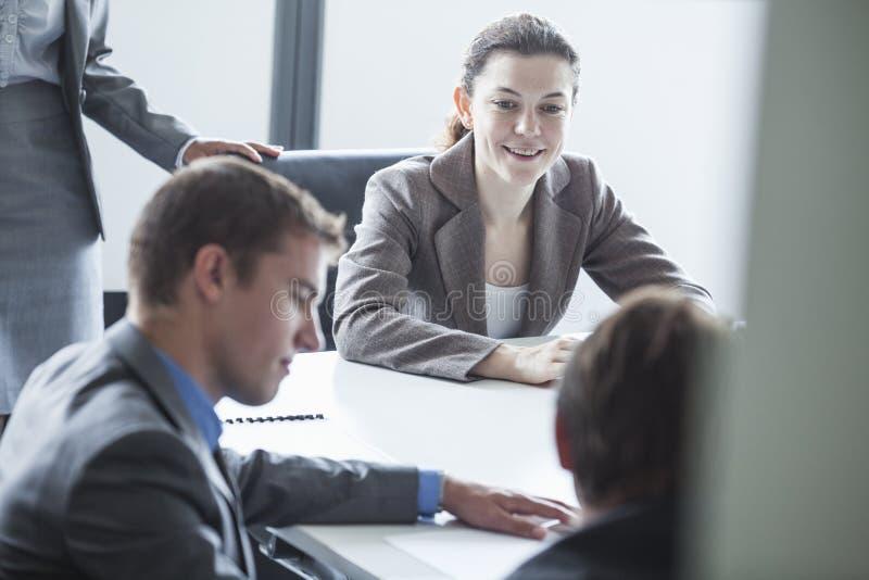 Cuatro hombres de negocios sonrientes que se sientan en una tabla y que tienen una reunión de negocios en la oficina fotografía de archivo