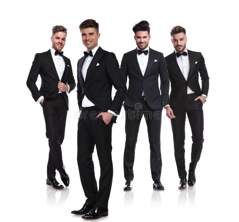 Cuatro hombres elegantes en los tuxedoes que se colocan con las manos en bolsillos fotos de archivo