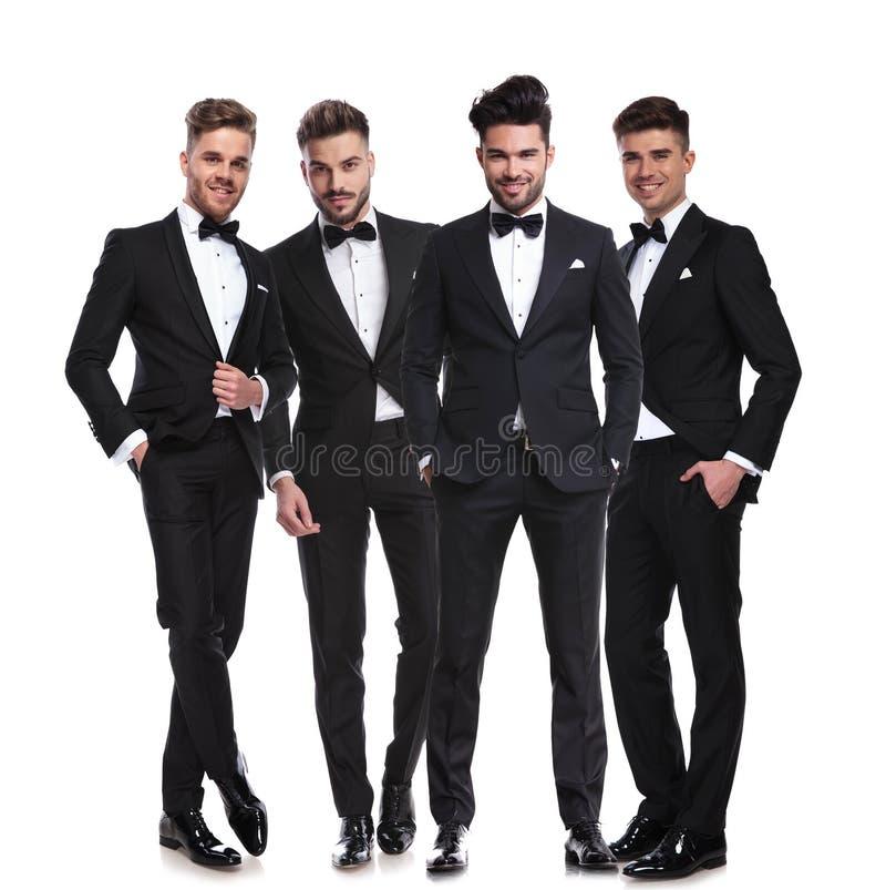 Cuatro hombres jovenes elegantes en los smokinges que se unen fotos de archivo