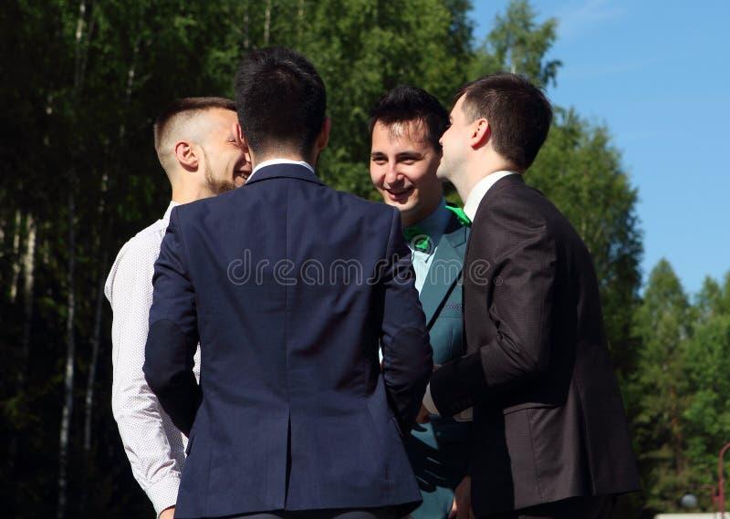 Cuatro hombres jovenes que hablan el uno al otro y que ríen imagen de archivo libre de regalías