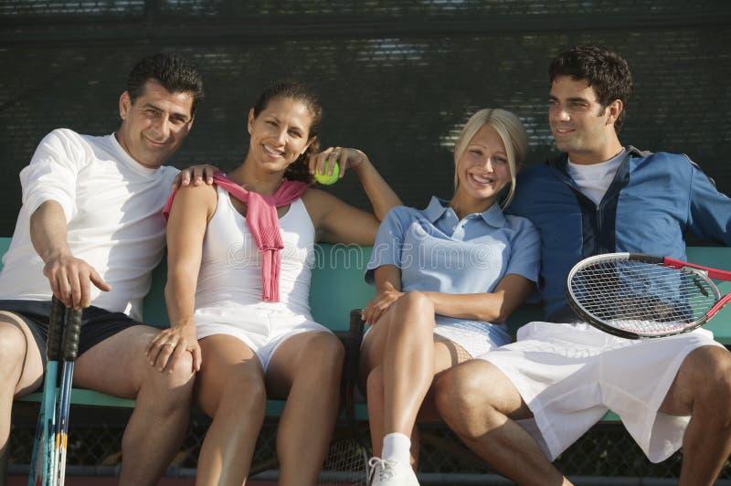 Cuatro jugadores de tenis de los dobles mezclados en banco imagen de archivo libre de regalías