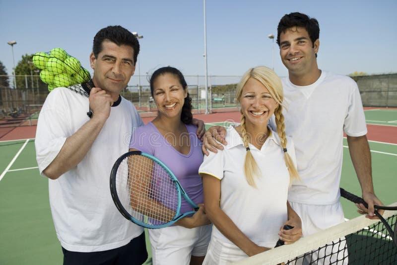 Cuatro jugadores de tenis de los dobles mezclados en la red fotografía de archivo