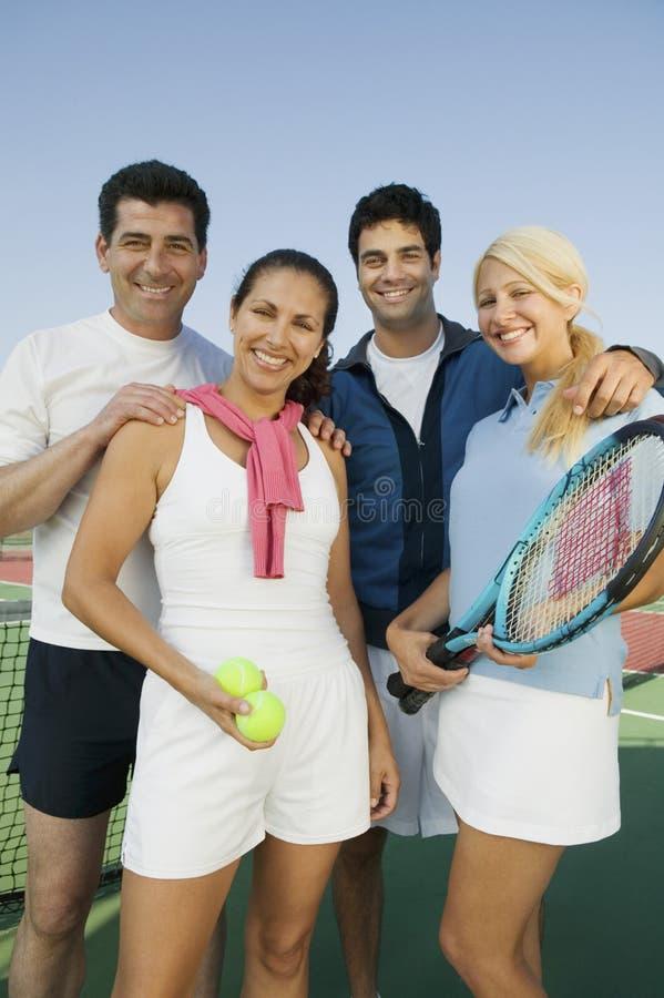 Cuatro jugadores de tenis de los dobles mezclados por la red en el retrato del campo de tenis fotos de archivo libres de regalías