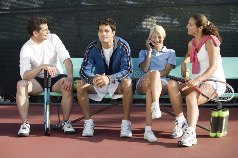 Cuatro jugadores de tenis de los dobles mezclados que se sientan en la vista delantera del campo de tenis imagen de archivo libre de regalías