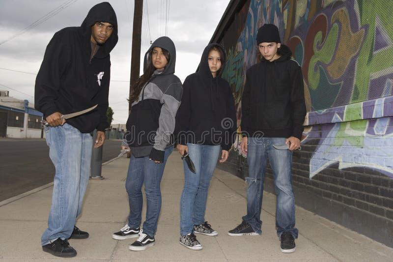 Cuatro ladrones enojados jovenes con los cuchillos imagenes de archivo