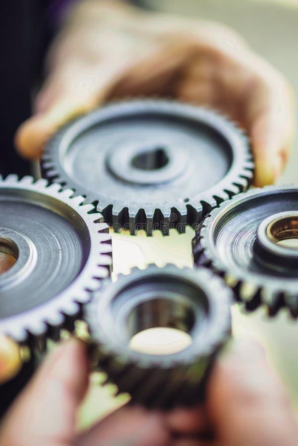 Cuatro manos conectan pedazos de rueda dentada del metal imágenes de archivo libres de regalías
