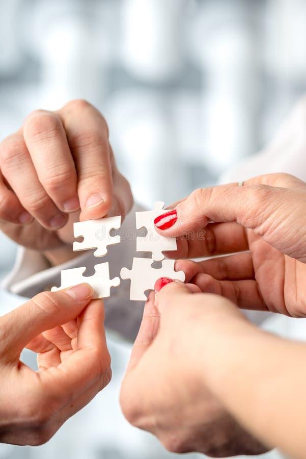 Cuatro manos que caben juntos hacer juego pedazos del rompecabezas que entrelazan foto de archivo libre de regalías