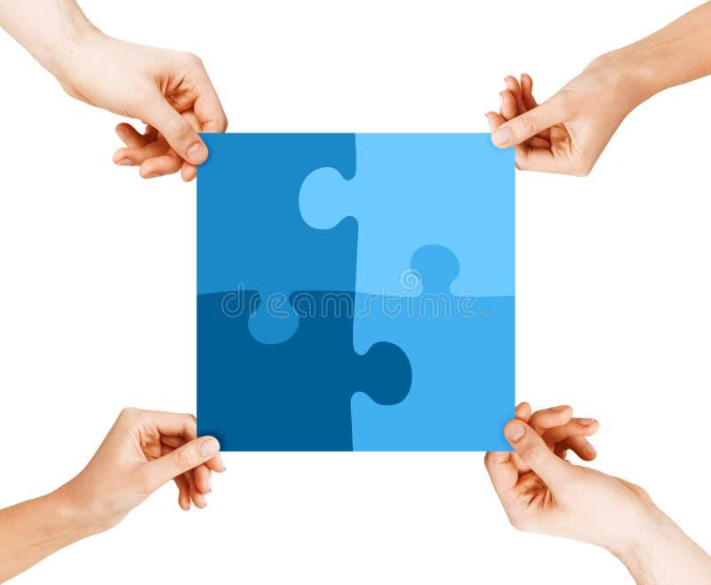 Cuatro manos que conectan pedazos del rompecabezas fotografía de archivo libre de regalías