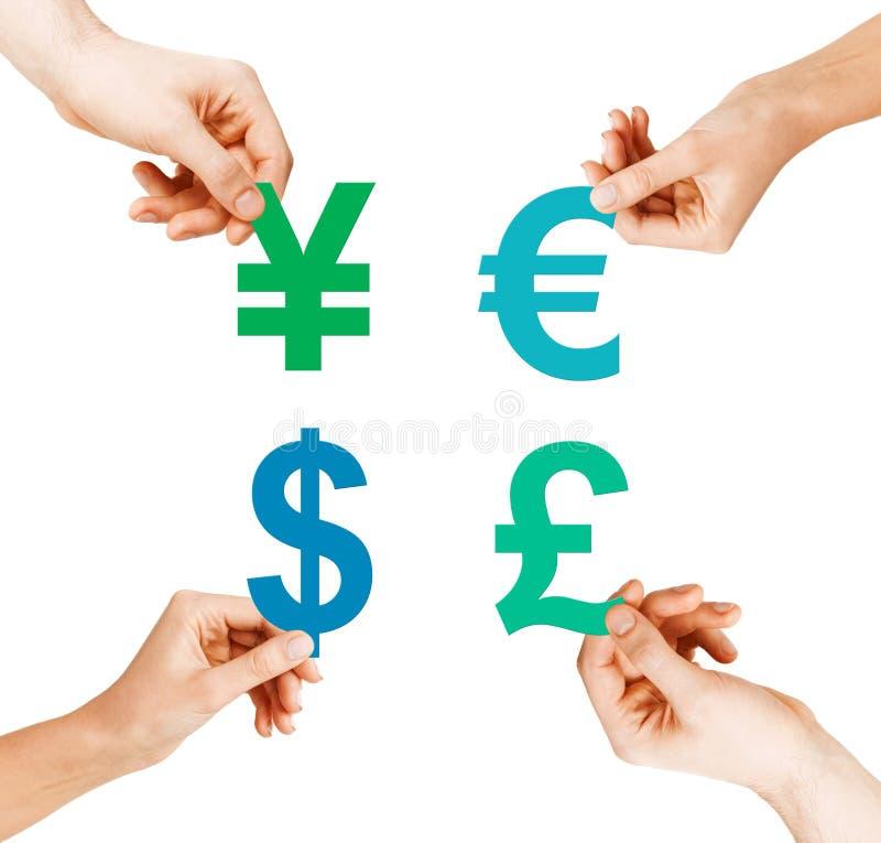 Cuatro manos que llevan a cabo símbolos de moneda fotos de archivo