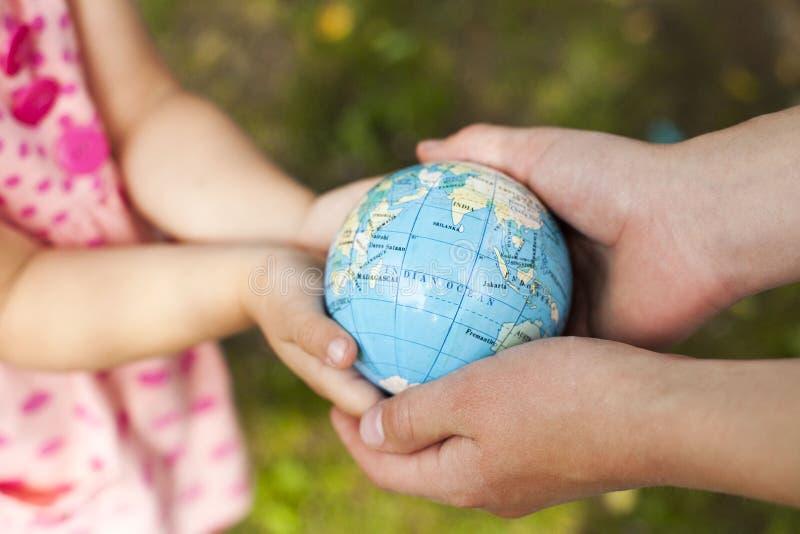 Cuatro manos, sosteniendo el globo fotografía de archivo