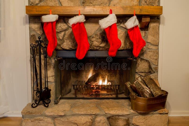 Cuatro medias de la Navidad colgaron por la chimenea con cuidado imagenes de archivo