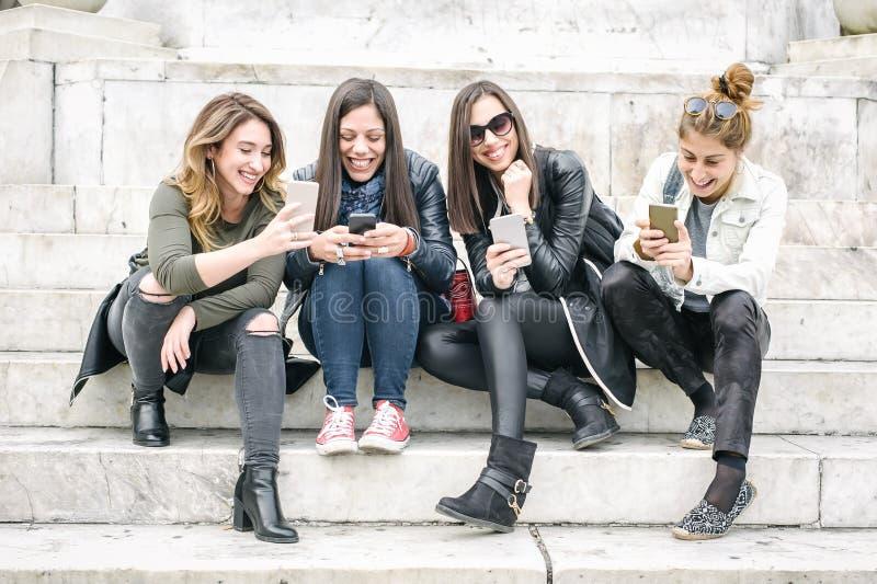 Cuatro medios sociales de observación felices de Internet de las amigas en smartp fotos de archivo