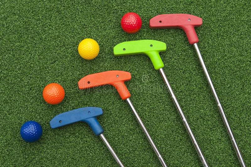 Cuatro Mini Golf Putters y bolas imagen de archivo libre de regalías