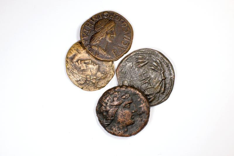 Cuatro monedas viejas con los retratos en un fondo blanco foto de archivo libre de regalías