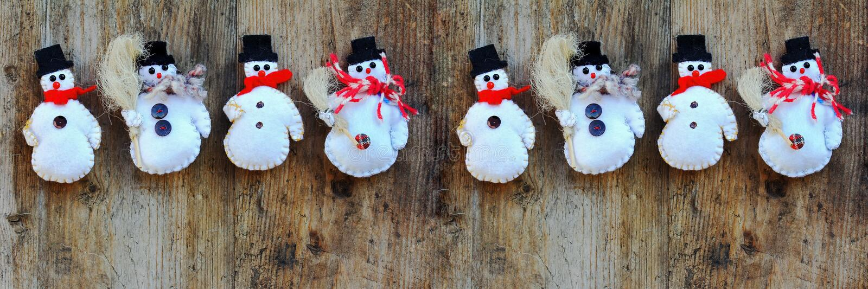 Cuatro muñecos de nieve en un fondo de madera foto de archivo