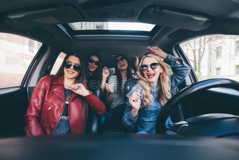 Cuatro mujeres alegres jovenes hermosas que miran uno a con sonrisa mientras que se sienta en coche imagenes de archivo