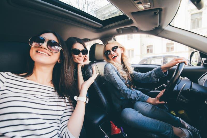 Cuatro mujeres alegres jovenes hermosas que miran uno a con sonrisa mientras que se sienta en coche imagen de archivo libre de regalías