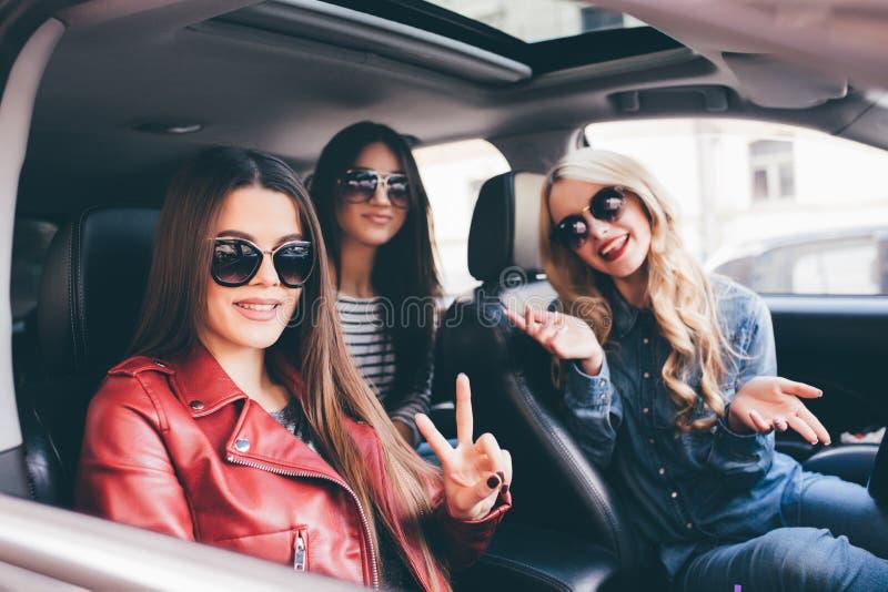 Cuatro mujeres alegres jovenes hermosas que miran uno a con sonrisa mientras que se sienta en coche fotos de archivo libres de regalías