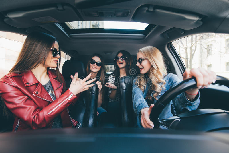 Cuatro mujeres alegres jovenes hermosas que parecen felices y juguetonas mientras que se sienta en coche fotos de archivo