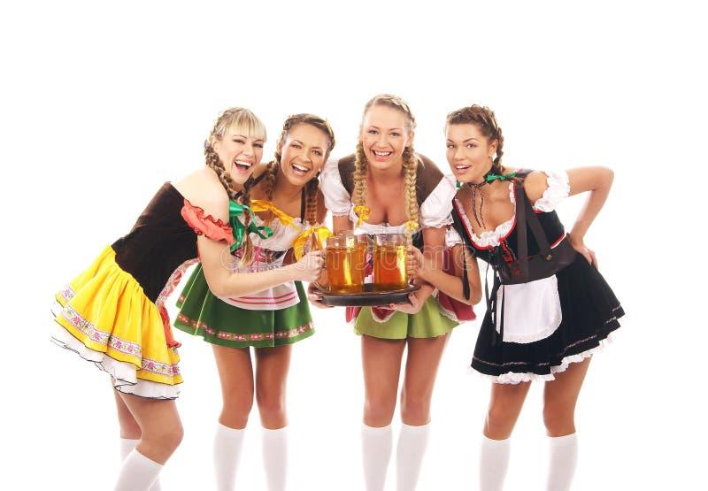 Cuatro mujeres jovenes en la ropa bávara que sostiene la cerveza imágenes de archivo libres de regalías
