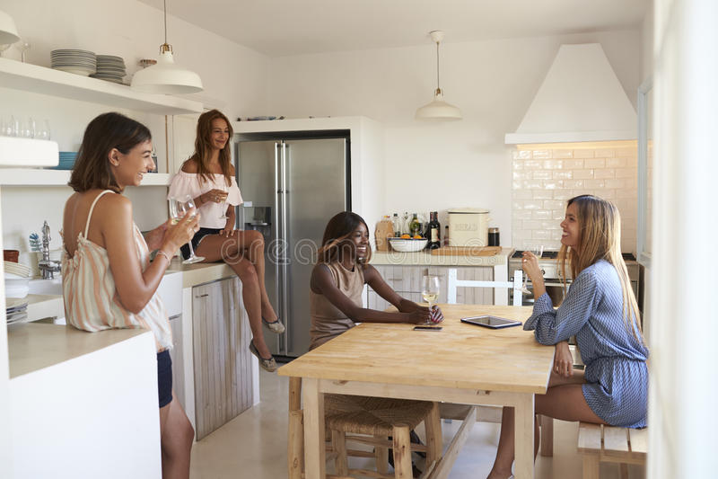 Cuatro mujeres que beben el vino en cocina durante una noche del ½ del ¿del girlsï adentro fotografía de archivo libre de regalías