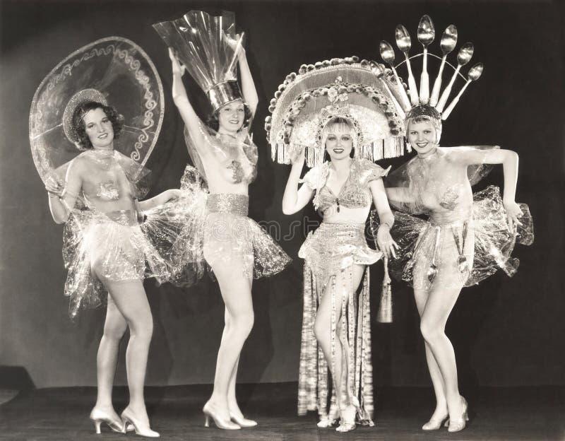 Cuatro mujeres que llevan los sombreros y los trajes divertidos fotografía de archivo
