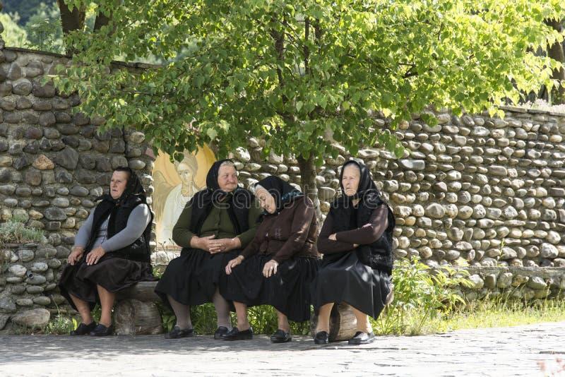 cuatro mujeres que se sientan en un banco en Rumania imagen de archivo libre de regalías