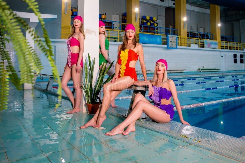 Cuatro mujeres rubias en trajes de baño coloridos en la piscina imagenes de archivo