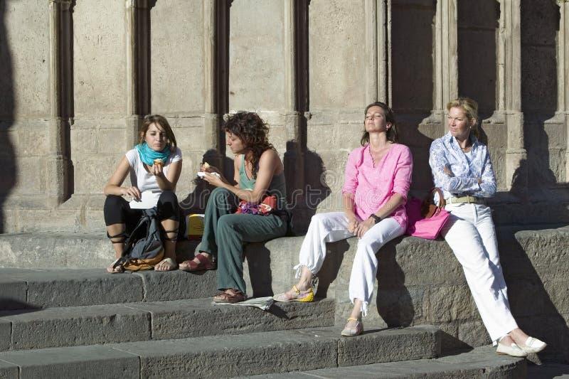 Cuatro mujeres se relajan en luz del sol de Barcelona vieja en el área de Barri Gotic, el cuarto gótico, España foto de archivo libre de regalías