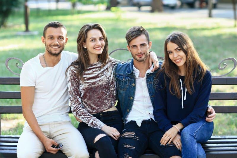Cuatro mujeres y hombres que se sientan en banco en abrazo fotos de archivo libres de regalías