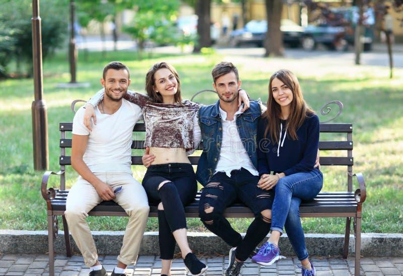 Cuatro mujeres y hombres que se sientan en banco en abrazo imagenes de archivo