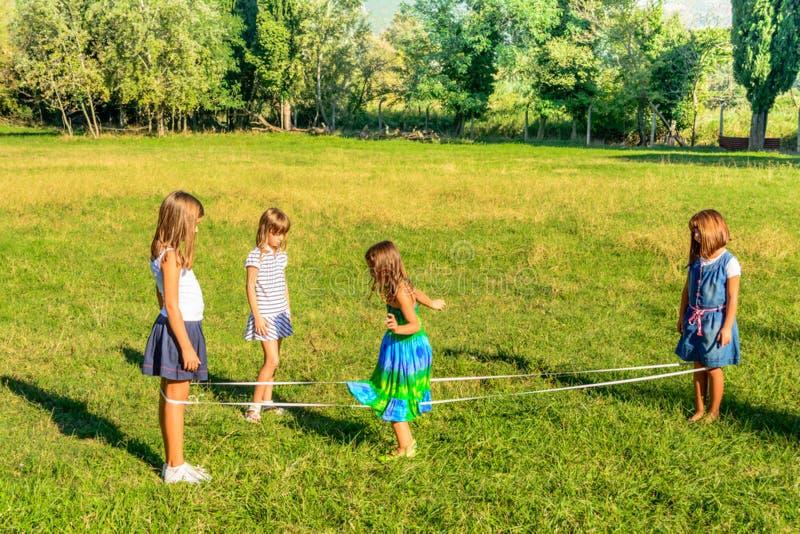Cuatro niñas que juegan los elástico en el parque fotografía de archivo
