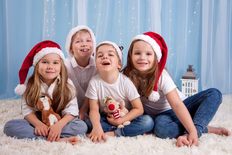 Cuatro niños adorables, niños preescolares, divirtiéndose para la Navidad foto de archivo