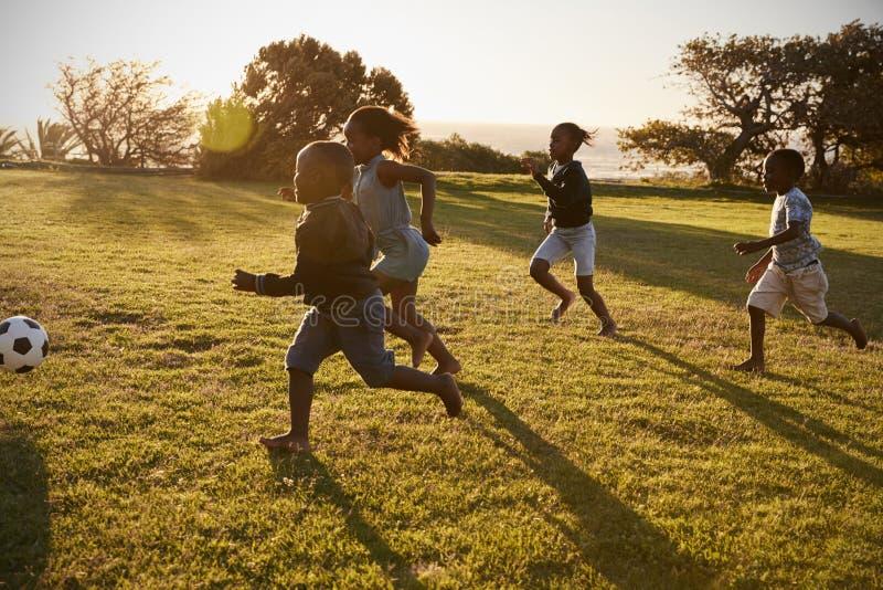 Cuatro niños de la escuela primaria que juegan a fútbol en un campo imágenes de archivo libres de regalías