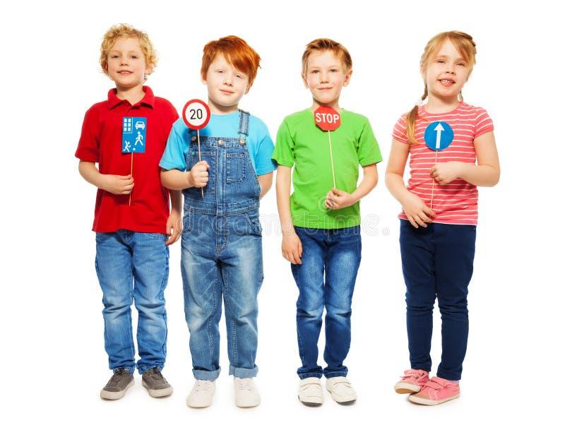 Cuatro niños felices que estudian la seguridad de las reglas de tráfico imagen de archivo