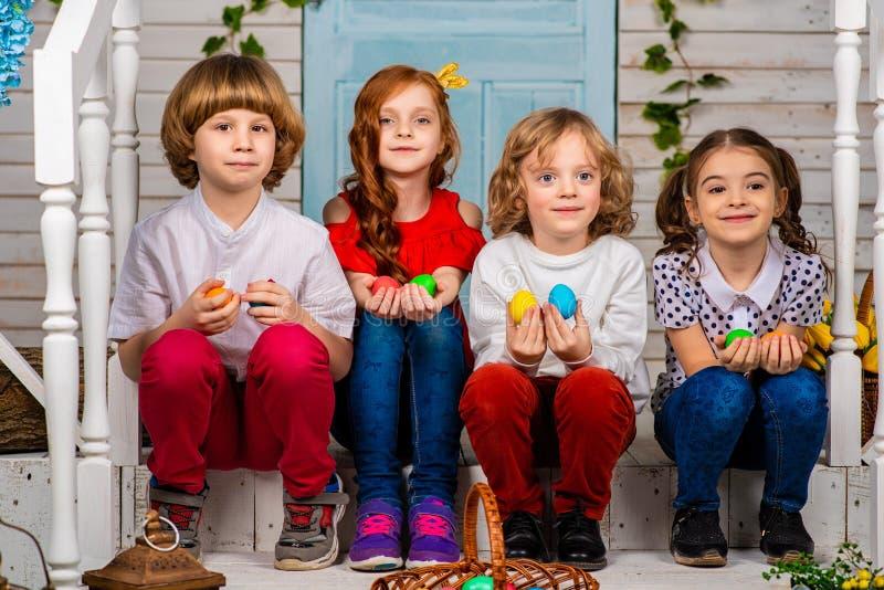 Cuatro niños hermosos, dos muchachos y dos muchachas se colocan en un umbral y una risa de madera imagen de archivo