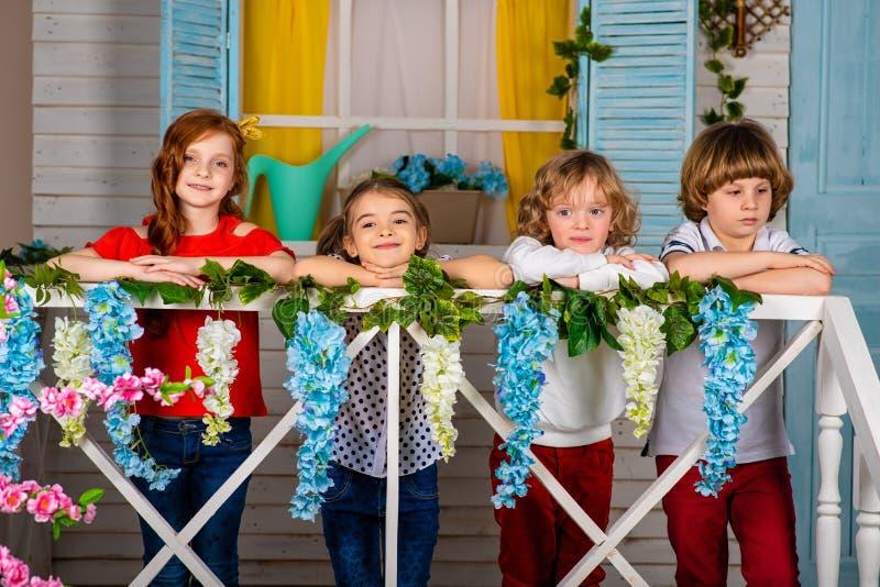 Cuatro niños hermosos, dos muchachos y dos muchachas se colocan en un umbral y una risa de madera fotos de archivo libres de regalías