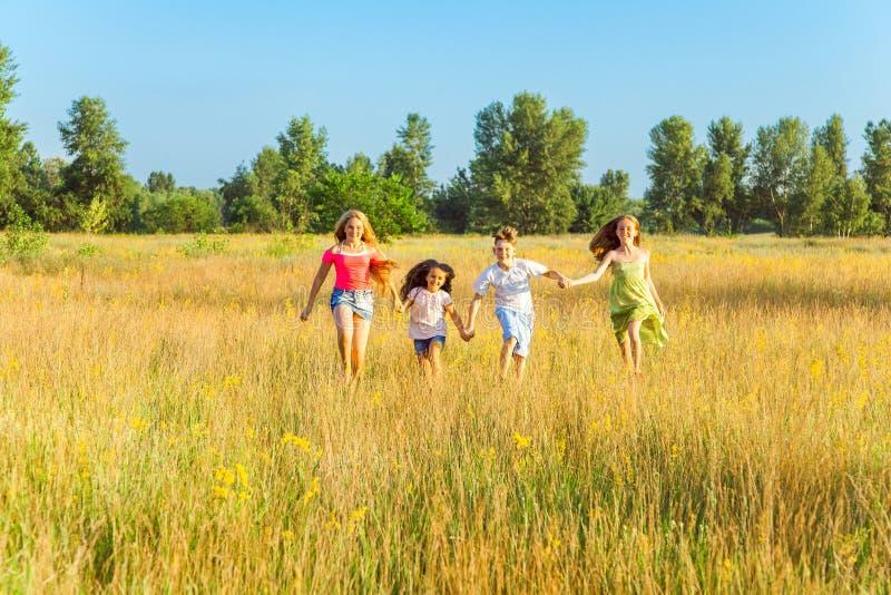 Cuatro niños hermosos felices que corren jugando acercar en el día de verano hermoso fotos de archivo libres de regalías