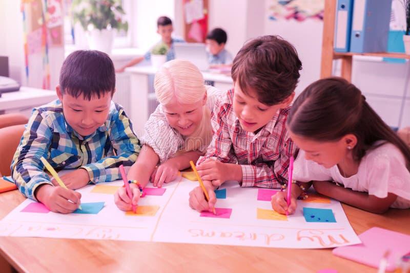 Cuatro niños que escriben junto en un périódico imagen de archivo libre de regalías