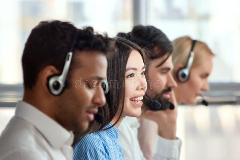 Cuatro operadores del teléfono de la ayuda en el lugar de trabajo imagenes de archivo