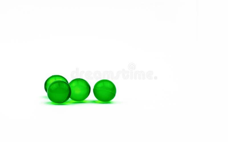 Cuatro píldoras suaves redondas verdes de la cápsula aisladas en el fondo blanco con el espacio de la copia Medicina de Ayurvedic fotografía de archivo libre de regalías