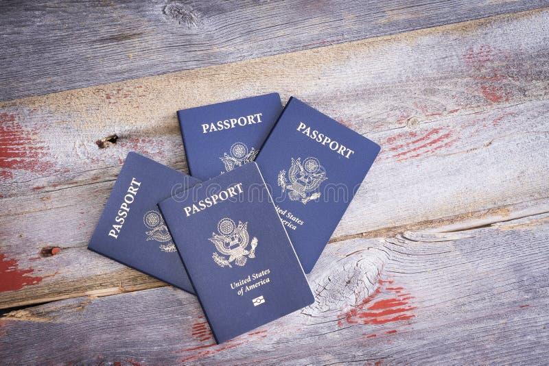 Cuatro pasaportes de Estados Unidos en una tabla de madera imagen de archivo