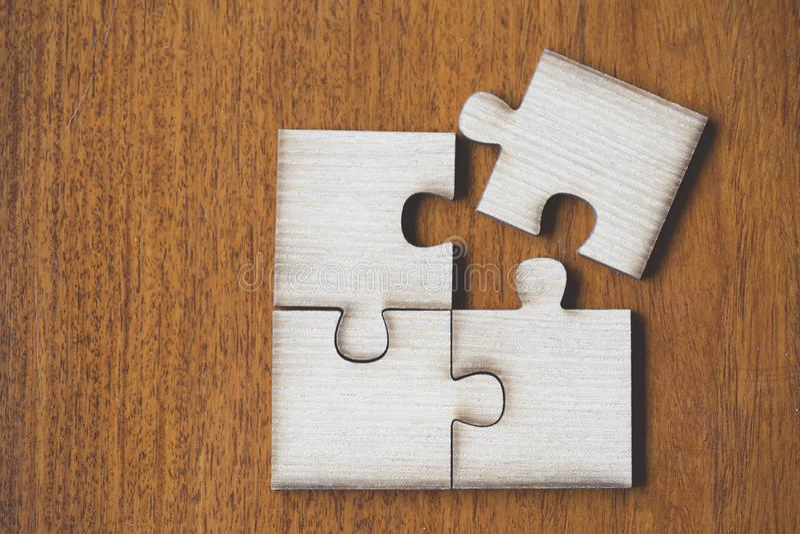 4 cuatro pedazos marrones de rompecabezas en la tabla de madera, pedazo pasado de plantilla imagen de archivo libre de regalías
