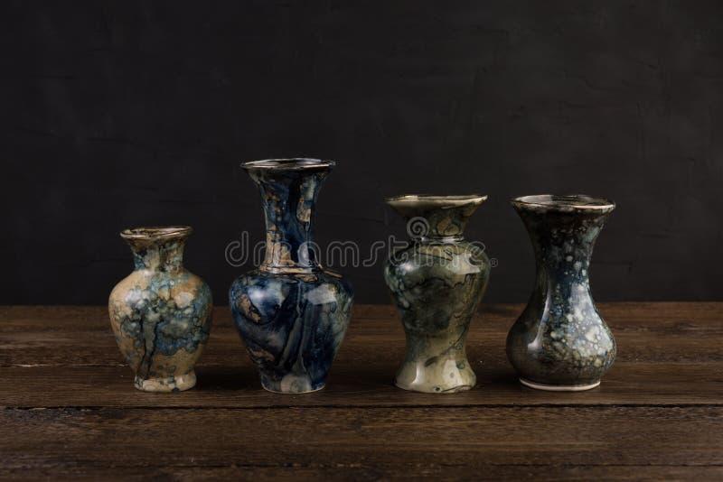 Cuatro pequeños floreros de mármol en la tabla de madera imagen de archivo