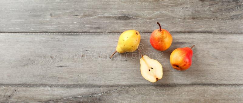 Cuatro peras maduras, una cortaron por la mitad, opinión de sobremesa, bandera ancha FO fotografía de archivo libre de regalías