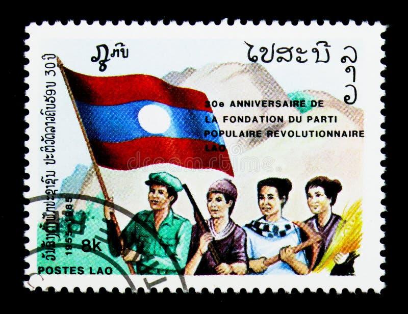 Cuatro personas con la bandera, el partido revolucionario popular, trigésimo anniv fotos de archivo libres de regalías