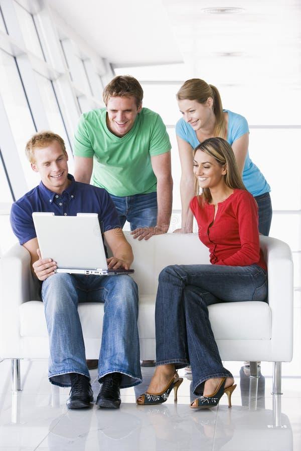 Cuatro personas en el pasillo que mira la sonrisa de la computadora portátil imagenes de archivo